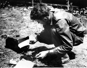 Message center code operator burns classified material in order to maintain maximum security. Note improvised incinerator made of discarded tin can.